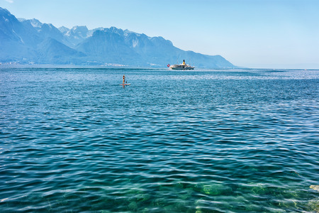 Montreux, Switzerland - August 27, 2016: Surfer on stand up paddle board and Excursion ship on Geneva Lake of Montreux, Swiss Riviera