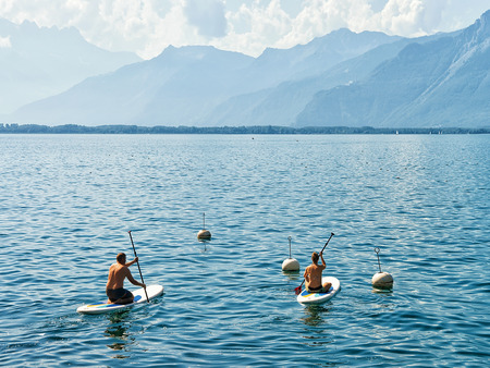 Montreux, Switzerland - August 27, 2016: People on Standup paddle surfing board on Geneva Lake in Montreux, Swiss Riviera Editorial