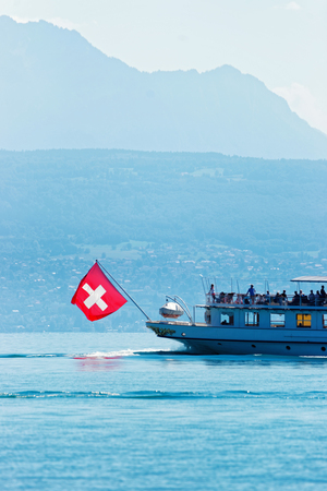 Water ferry ship with Swiss flag on Lake Geneva at Ouchy embankment in Lausanne, Switzerland. People aboard Stock Photo