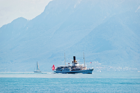 Excursion water ferry with Swiss flag on Lake Geneva at Ouchy embankment in Lausanne, Switzerland. People aboard Stock Photo