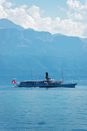 Water ferry ship with Swiss flag in Lake Geneva at Ouchy embankment in Lausanne, Switzerland. People aboard