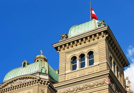 Fragment of Federal Palace of Switzerland with towers and Swiss flag in Bern, Switzerland