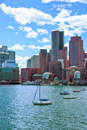 Sailing boats traveling across Charles river with the skyline of the city in the background in Boston, America