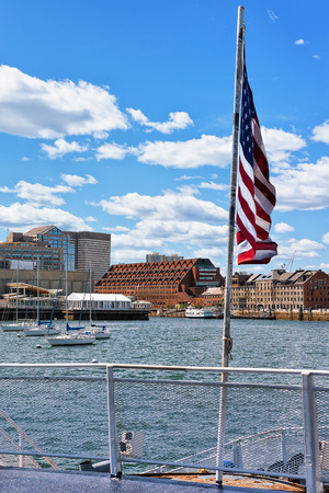 Beautiful city waterfront and skyline and US flag in Boston, MA, America