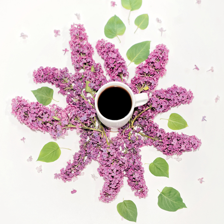 Cup of coffee and violet lilac flowers on the white background. Flat lay, top view