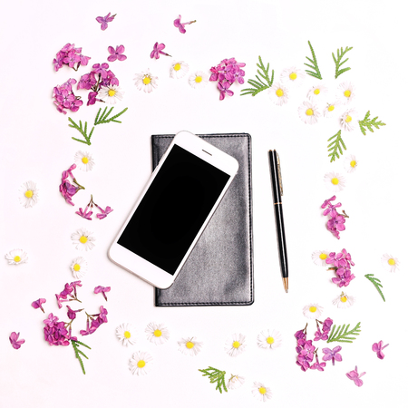 personal organiser: Pattern with mobile phone, notebook, pen and lilac flowers on the white table background. Flat lay, top view