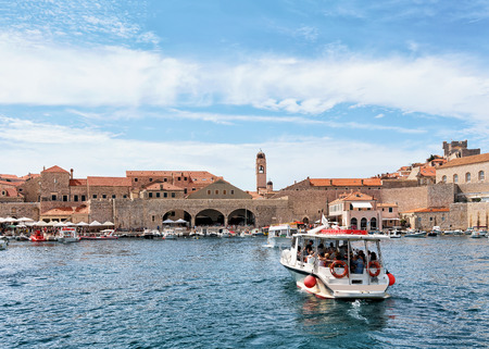 ragusa: Dubrovnik, Croatia - August 19, 2016: Water ferry with people at the Old port and people in the Adriatic Sea in Dubrovnik, in Croatia. Editorial