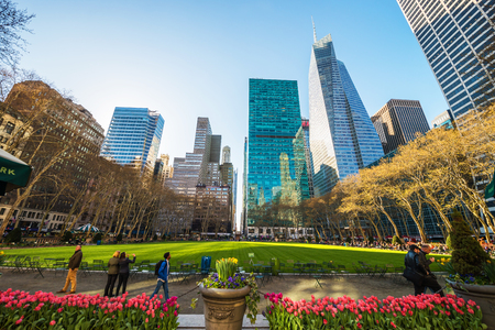 New York, USA - April 24, 2015: Skyline with Skyscrapers and tourists of Bryant Park in Midtown Manhattan, New York, NYC, USA. Tourists relaxing in the park