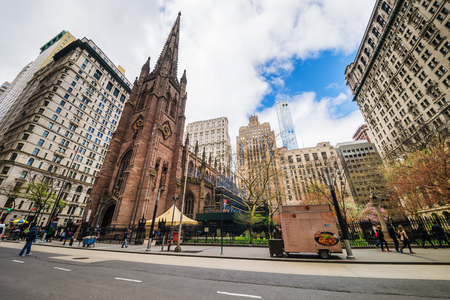 New York, USA - April 24, 2015: Street with tourists and traffic and Trinity Church in Manhattan, New York, NYC, USA. It is a historic parish church near Wall Street and Broadway. Editorial