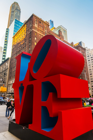 New York, USA - May 6, 2015: Love sculpture by American artist Robert Indiana and tourists passing by in Midtown Manhattan in New York, NYC, USA. The famous monument is located on 6th Avenue. Editorial