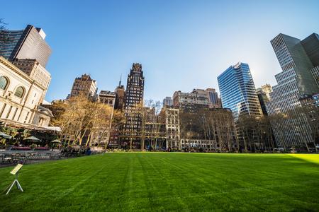 ミッドタウンマンハッタンのブライアントパークの緑の芝生と超高層ビル、ニューヨーク、ニューヨーク、アメリカ合衆国。公園でくつろぐ観光客 報道画像