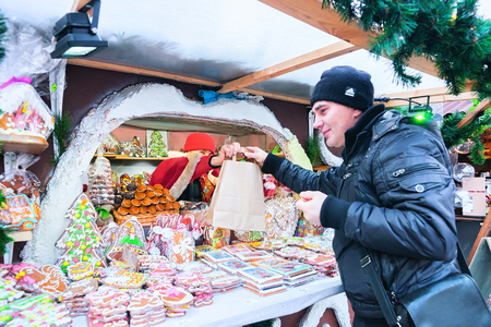 Riga, Latvia - December 28, 2016: Man at the stall on Christmas Market at Dome Square in Riga Old Town in winter