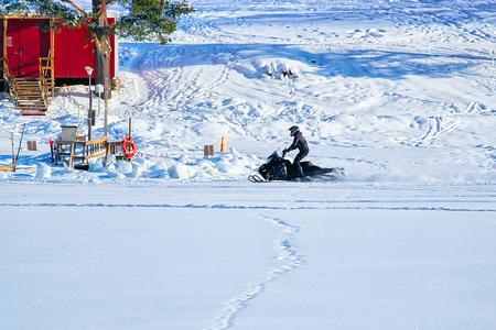 冬ロヴァニエミ、フィンランドのラップランドでアイスの湖でスノーモービルに乗って男