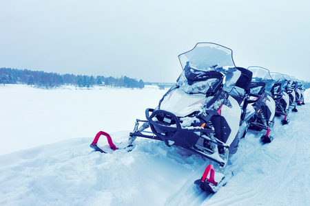 冬ロヴァニエミ、フィンランドのラップランドで凍った湖でスノーモービル