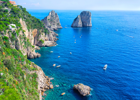 Ships at Faraglioni cliffs and Tyrrhenian Sea on Capri Island, Italy