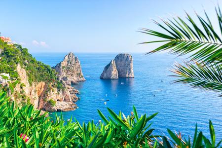 Ships at Faraglioni cliffs and Tyrrhenian Sea of Capri Island, Italy Stock Photo