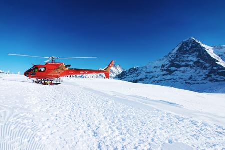 Mannlichen, Switzerland - December 31, 2013: Red helicopter at Swiss Alpine mountain Mannlichen in winter, of Switzerland