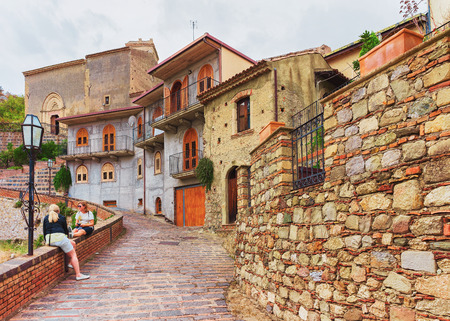 Savoca, Italy - September 27, 2017: Tourists in the cozy street of Savoca village, Sicily, Italy