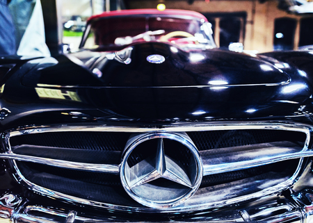 Berlin, Germany - December 11, 2017: Emblem and radiator grill of black Retro Mercedes Benz SL car in the garage in Berlin, Germany