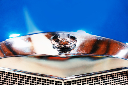 Emblem and radiator grill in blue Retro car in the garage in Berlin, Germany