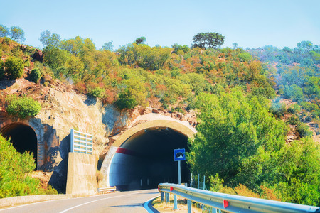 Car on the road with underpass in Carbonia Iglesias province, Sardinia, Italy