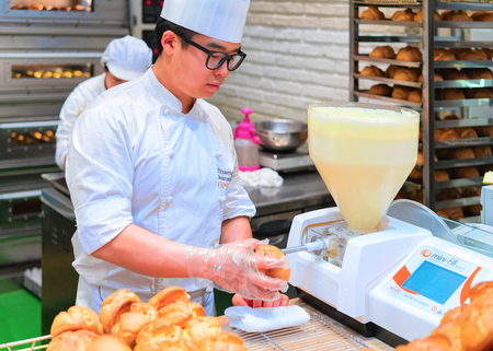 Busan, South Korea - March 13, 2016: Pastryman putting cream into the puffs in the food corner at the shopping mall in Busan, South Korea
