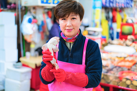Busan, South Korea - March 13, 2016: Woman selling a shark in Fish market in Jagalchi in Busan, South Korea Editorial