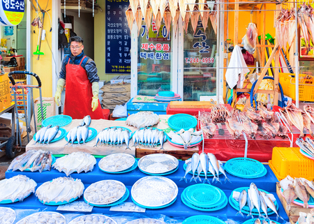 Busan, South Korea - March 12, 2016: Seller of raw fish in Fish market in Jagalchi in Busan, South Korea