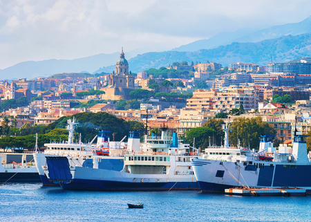 Passenger ferries in the Mediterranean Sea and cityscape of Messina, Sicily, Italy