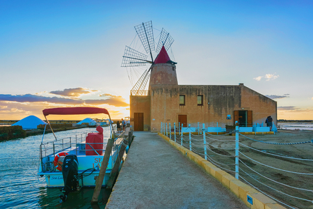 Marsala, Italy - September 19, 2017: Sunset at Windmill and the salt evoporation pond in Marsala, Sicily island in Italy