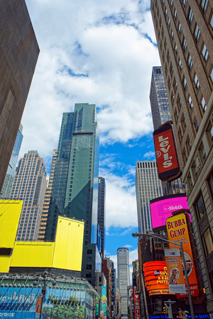 New York, USA - April 24, 2015: 7th Avenue and Broadway in Times Square. Skyscrapers in Midtown Manhattan in New York, NYC, the USA. Tourists in the street