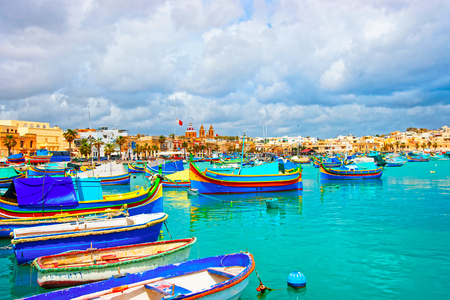Luzzu colorful boats, Marsaxlokk Port embankment in the bay of the Mediterranean sea, Malta island
