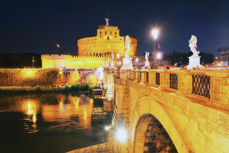 Rome, Italy - October 14, 2016: Castle of Holy Angel and Ponte Sant Angelo Bridge over the Tiber River, in Rome, Italy. It is is also called as the Bridge of Hadrian. Illuminated late in the evening Standard-Bild - 101833690