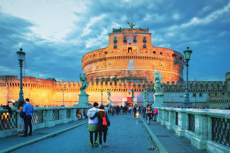 Rome, Italy - October 14, 2016: Couple on Ponte Sant Angelo Bridge  at Castle of Holy Angel, in Rome in Italy. It is is also called as the Bridge of Hadrian. Illuminated late in the evening Standard-Bild - 101889743