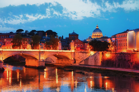 Dome of Saint Peters Basilica in Vatican city and Ponte Sant Angelo Bridge over the Tiber River, in Rome in Italy. It is is also called as the Bridge of Hadrian. Illuminated late in the evening