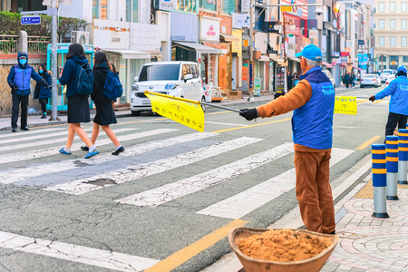 Busan, South Korea - March 14, 2016: Traffic controller helping children to cross the street in the city center of Busan in the morning, South Korea