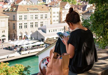 Zurich, Switzerland - September 2, 2016: Girl sitting on Lindenhof hill and reading a book in Zurich, Switzerland. Limmatquai on the background. Éditoriale