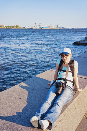 Young girl with digital camera sitting at the embankment of the Delaware River in Philadelphia, Pennsylvania, the USA. Stock Photo