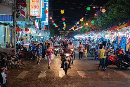 Can Tho, Vietnam - February 27, 2016: People on the Street market in Can Tho, in Vietnam, at night. Blurred focus