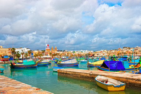 Luzzu colorful boats in Marsaxlokk Port embankment on the bay of the Mediterranean sea, Malta island Stock Photo