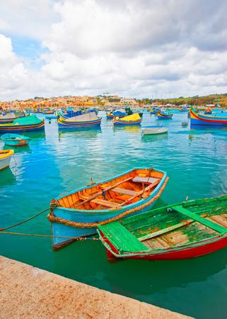 Luzzu colorful boats at Marsaxlokk Port in the bay of the Mediterranean sea, Malta island Фото со стока