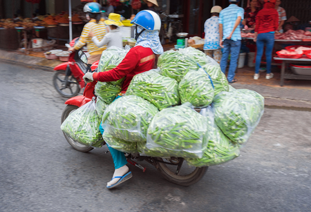 A Person on the scooter carrying a bilk of green peas in the street of Can Tho, in Vietnam Editoriali