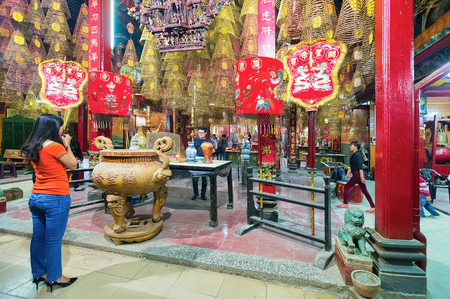 Can Tho, Vietnam - February 27, 2016: Woman praying in Ong Temple in Can Tho, in Vietnam Stock Photo - 101890095