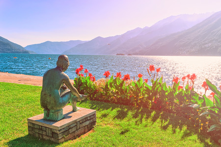 Ascona, Switzerland - August 23, 2016: Sitting woman sculpture at the promenade at the luxurious resort in Ascona on Lake Maggiore in Ticino canton in Switzerland. Sunlight toned Editorial