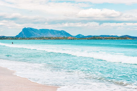 La Cinta beach and Blue waters of Mediterranean Sea in San Teodoro in Sardinia Island in Italy. Tavolara Island seen on the background. Imagens