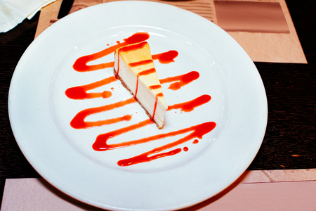 Cheese cake with strawberry toppinng sauce on the white plate in a restaurant. Imagens
