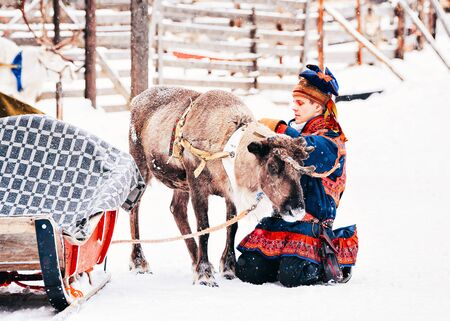 Rovaniemi, Finland - March 3, 2017: Man in Saami traditional costume at Reindeer in Finland in Lapland in winter.