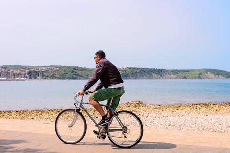 Izola, Slovenia - April 24, 2018: Man riding a bicycle at the embankment of the Adriatic Sea in Izola fishing village, Slovenia