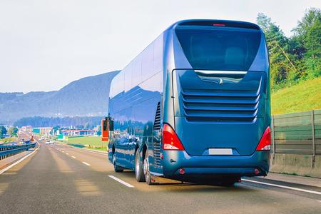 Bus touristique bleu sur la route en Pologne. Notion de voyage.