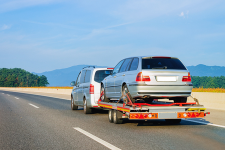 Car carrying trailer with new vehicle in the asphalt road in Slovenia. Stock Photo